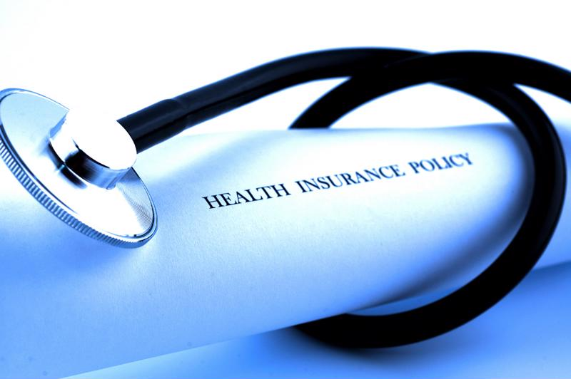 "Stethoscope wrapped around a rolled up paper with the words, ""Health Insurance Policy"" printed on the outside."