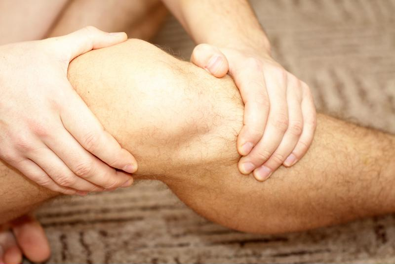 Man holding knee.