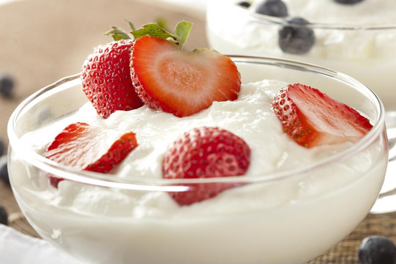 A bowl of yogurt is decorated with sliced strawberries.