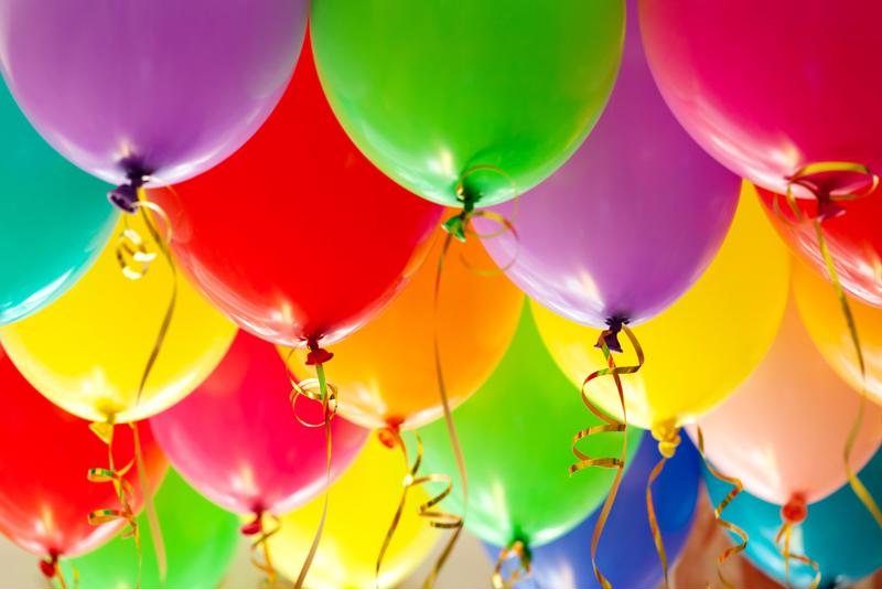Rainbow colored balloons filled with helium.