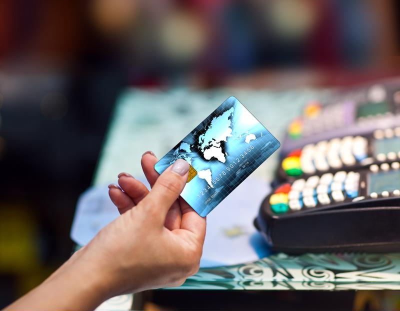 Consumer handing credit card with POS portals in the background.