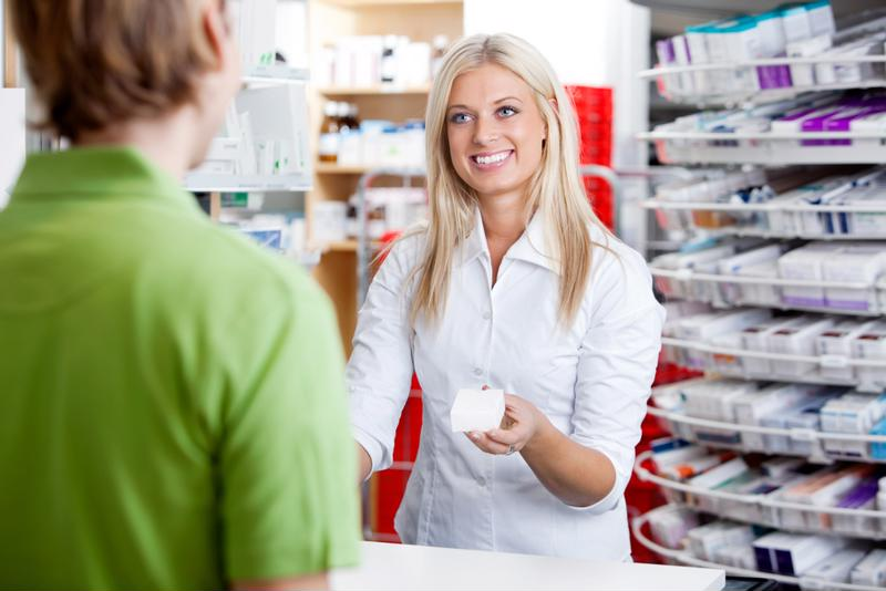 Female pharmacy technician holding out prescription card to customer.