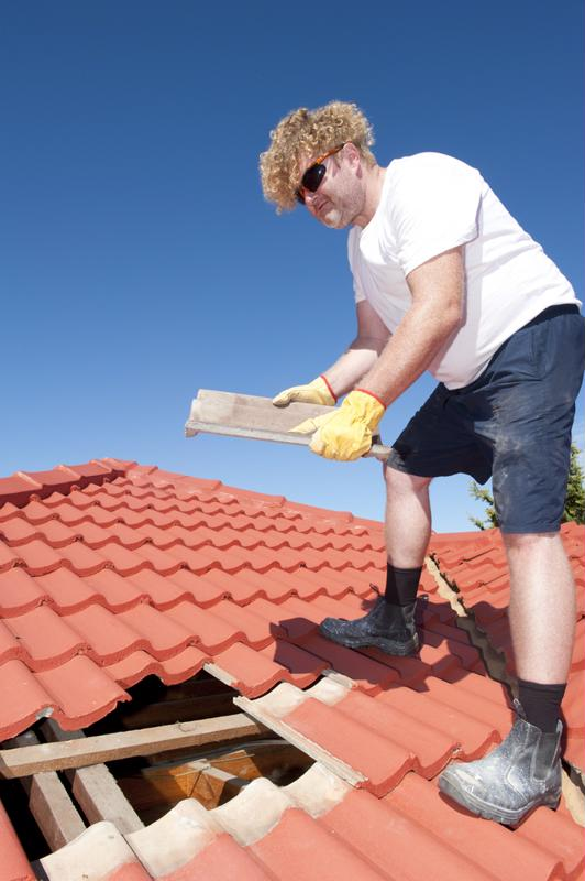 A man retiles his roof.