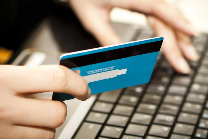 Consumer holding credit card above keyboard.