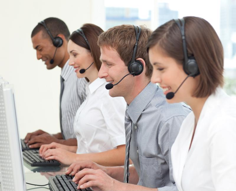 Row of people sitting at keyboards wearing headsets in a contact center.