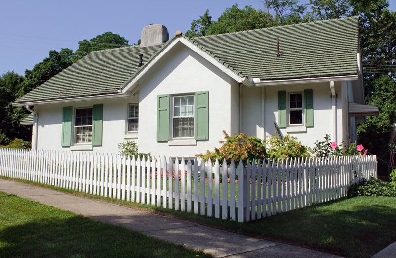 A home on a corner has a white picket fence surrounding the front yard.