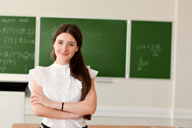 A woman teacher standing in front of a blackboard.