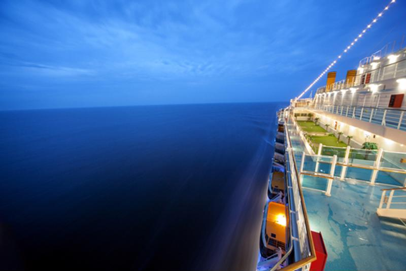 Top deck view of the side of a  cruise ship at sea.