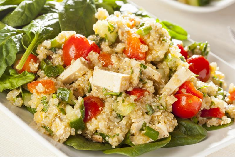 Serve hearty quinoa salad on top of spinach to give the meal more texture.