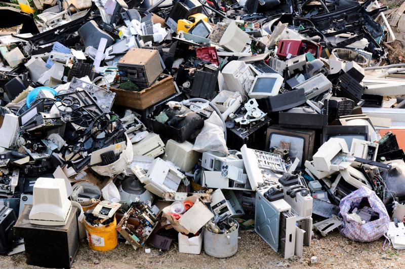 A pile of  old and broken electronics at a dump.