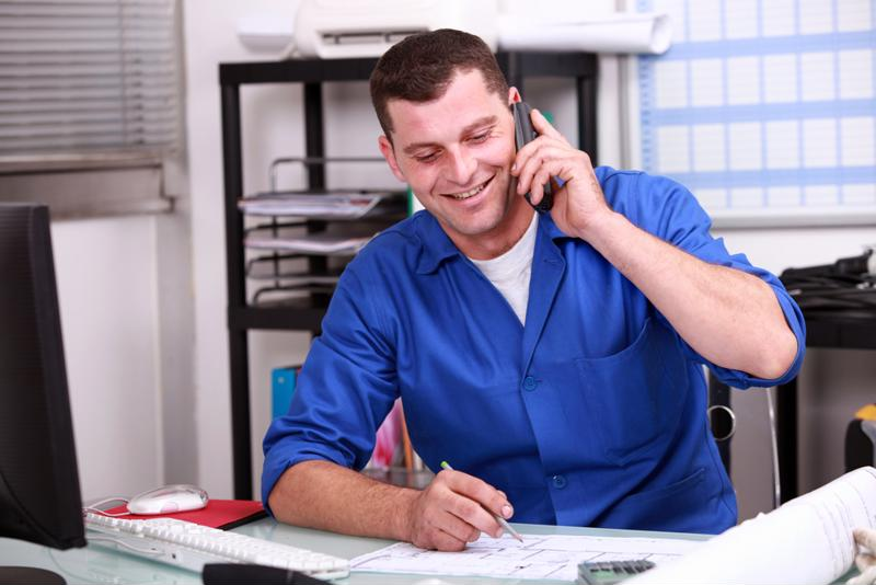 A contractor discusses details on the phone while consulting a desk calendar.