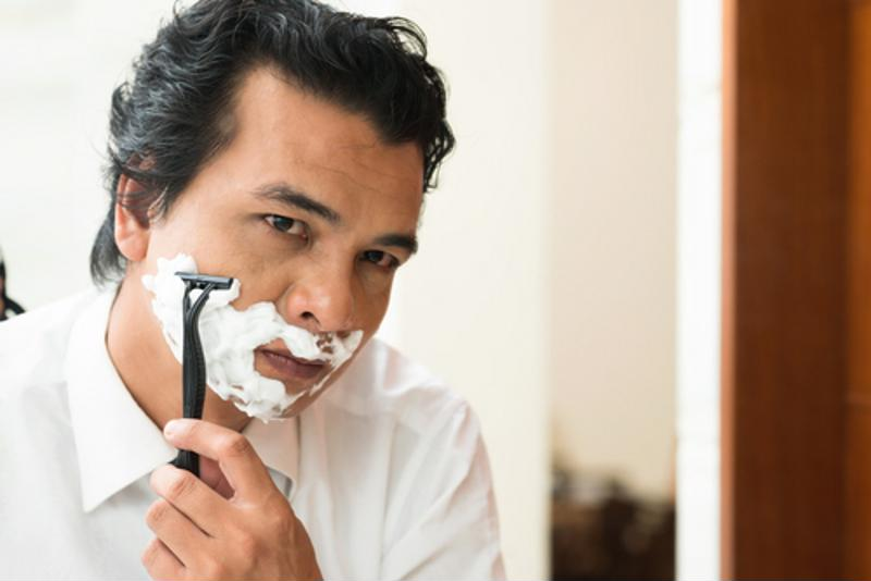 A man with shaving cream and a razor shaves his face.