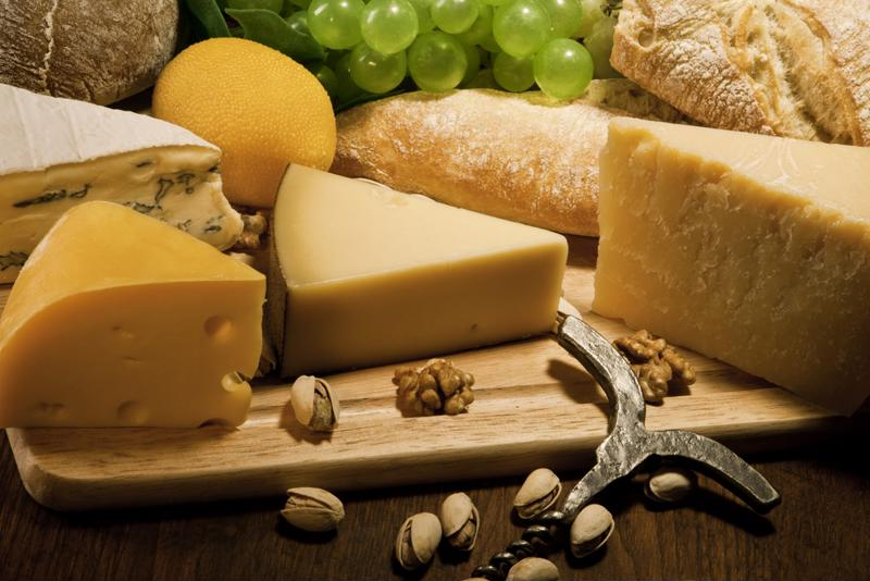 A cheese plate is filled with wedges of cheese, nuts and grapes.
