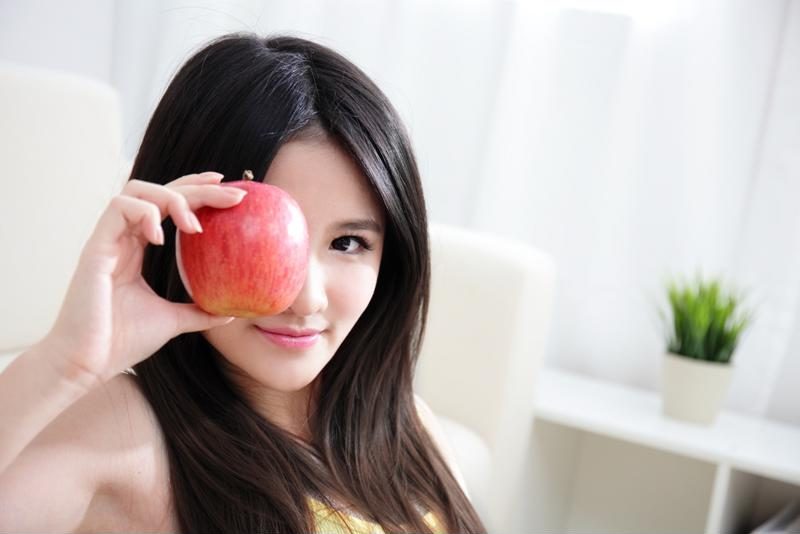 A young woman holding an apple up to her face.