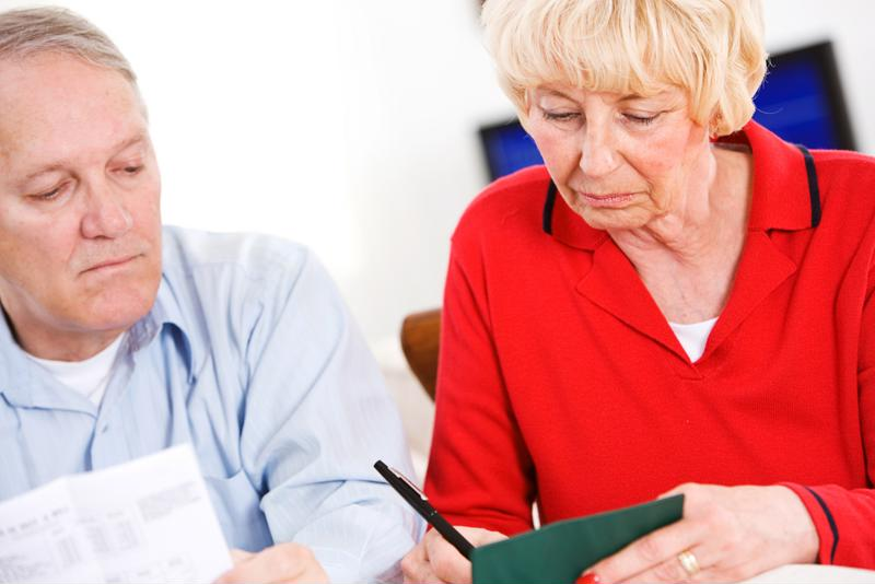 Senior woman writing in checkbook with man at her right.