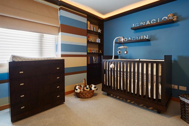 A nursery with a blue and dark brown color scheme.