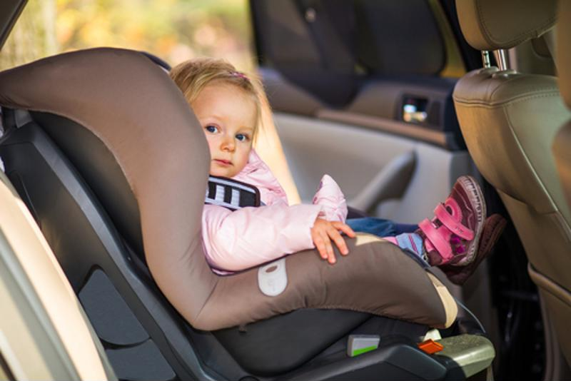 A little girl in a car seat.