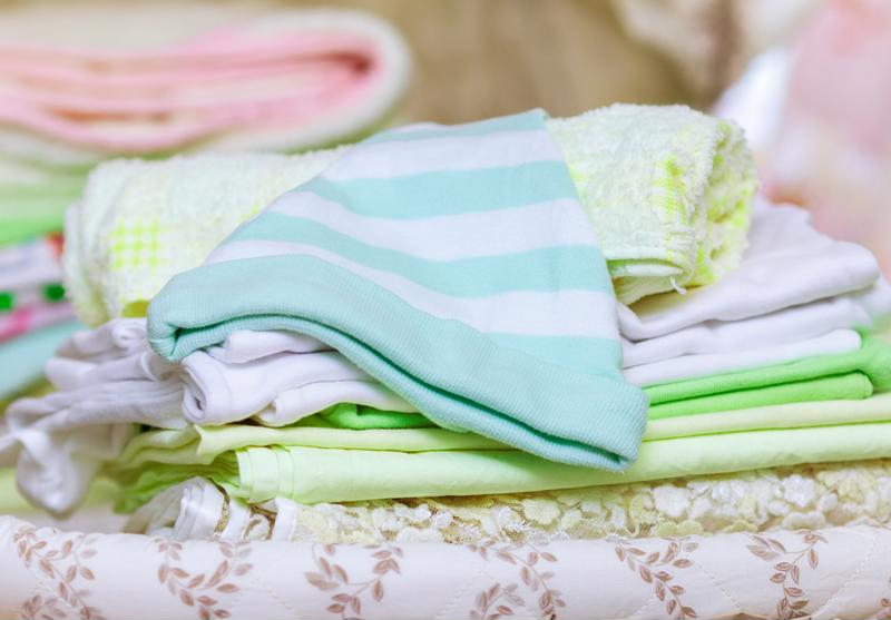 A pile of baby clothes in light shades of green, blue and pink.