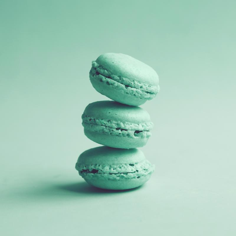 Three teal macarons stacked on top of each other.
