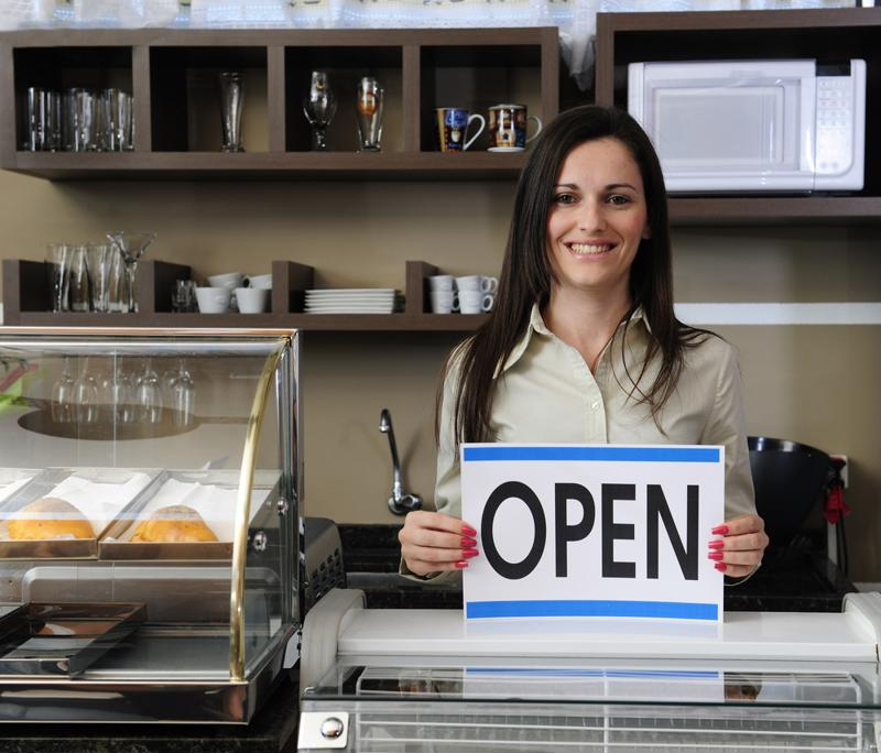 Small business owner at a coffee shop standing in front of counter holding OPEN sign.