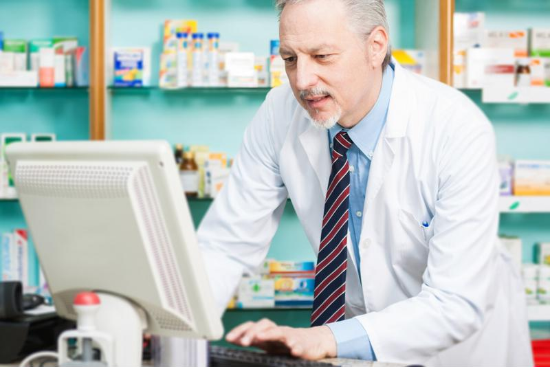 pharmacists typing on computer in pharmacy