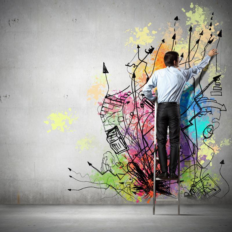 Man on a ladder painting graffiti art on a white wall.