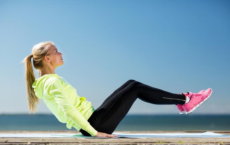 Chica haciendo yoga en la playa.