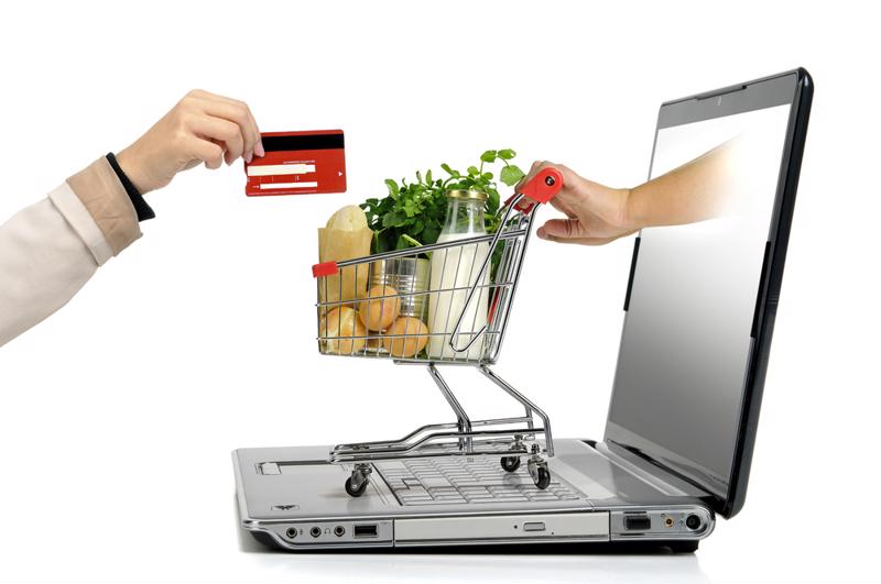 shopping cart, computer and online shopper's hand with credit card
