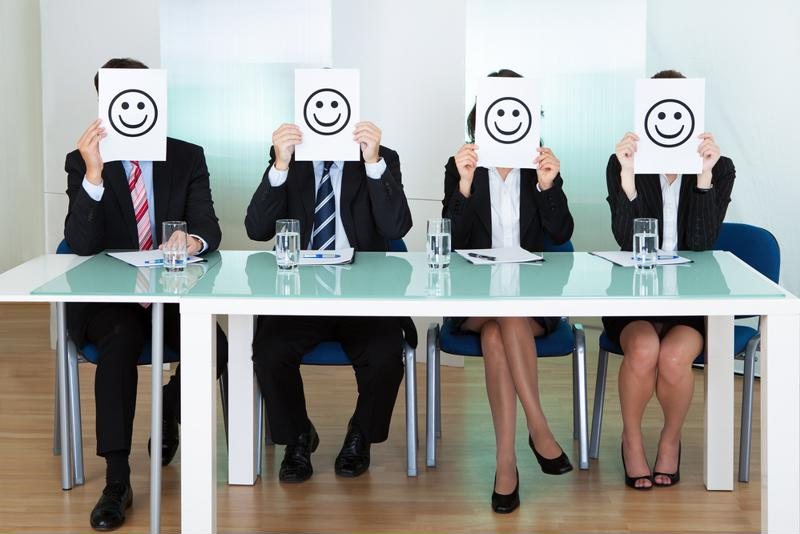 Corporate people sitting at a desk holding smiley face signs in front of their faces.