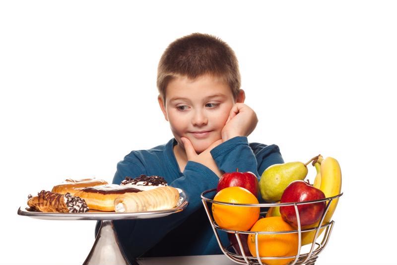 boy choosing between fruit and dessert