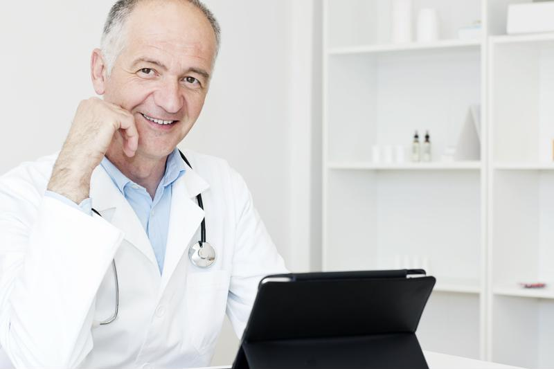 Doctor wearing coat and stethoscope working on a tablet.