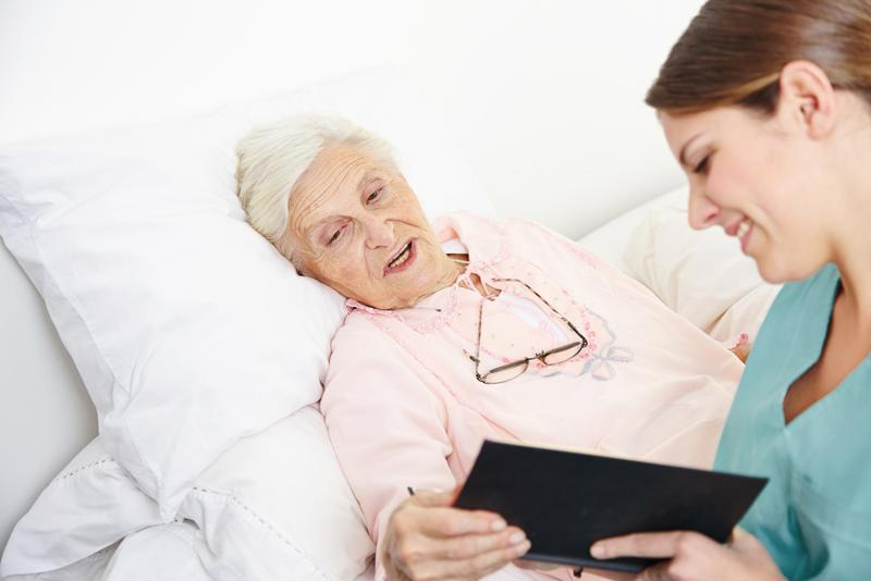 Woman in hospice talking to nurse.