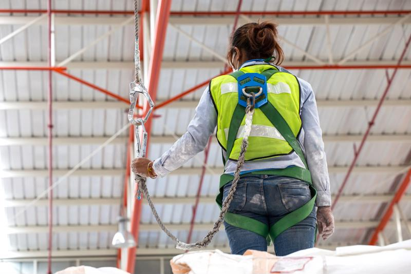 Worker wearing safety harness.