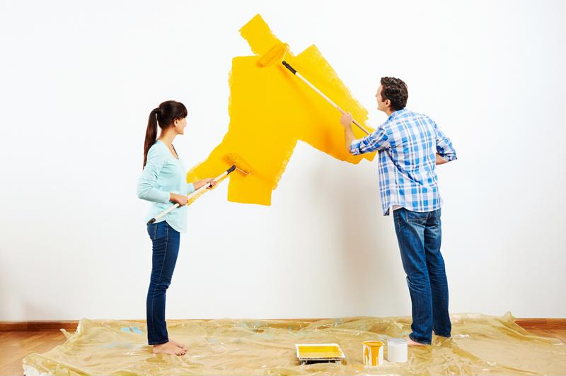 A couple painting walls a sunny yellow.