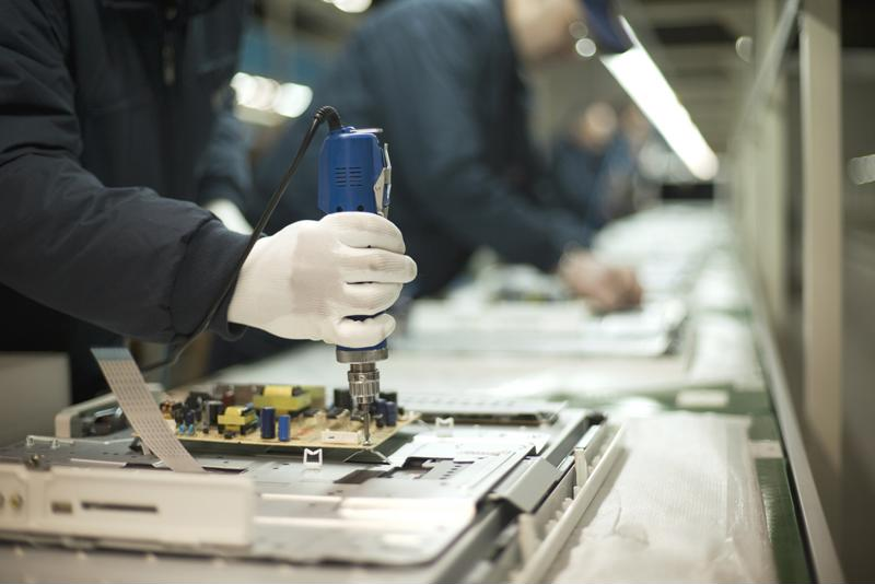 Manufacturing workers put together electronics products