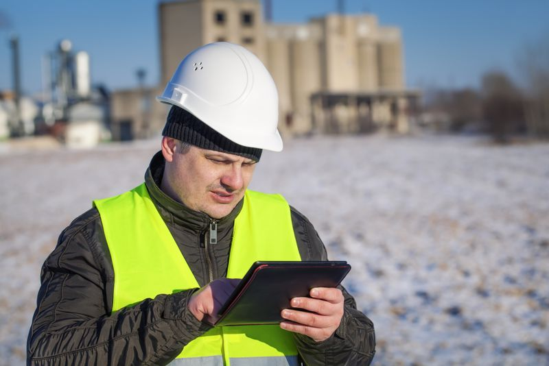 Factory worker standing in snow with digital tablet