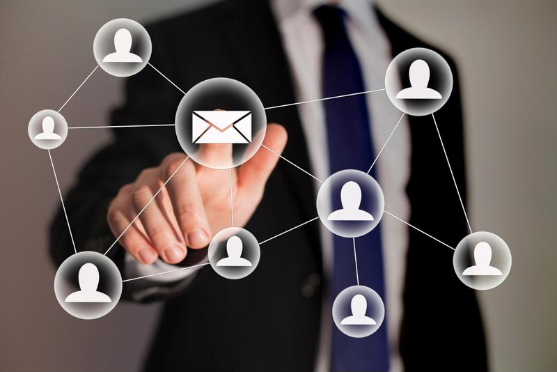 Man in suit pointing to envelope icon that is connected to individual people icons by white lines.