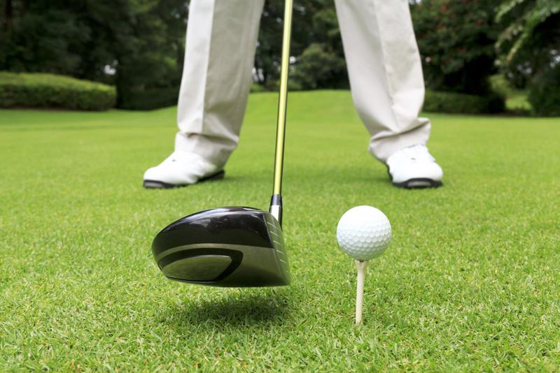 Man standing on golf course about to hit ball.