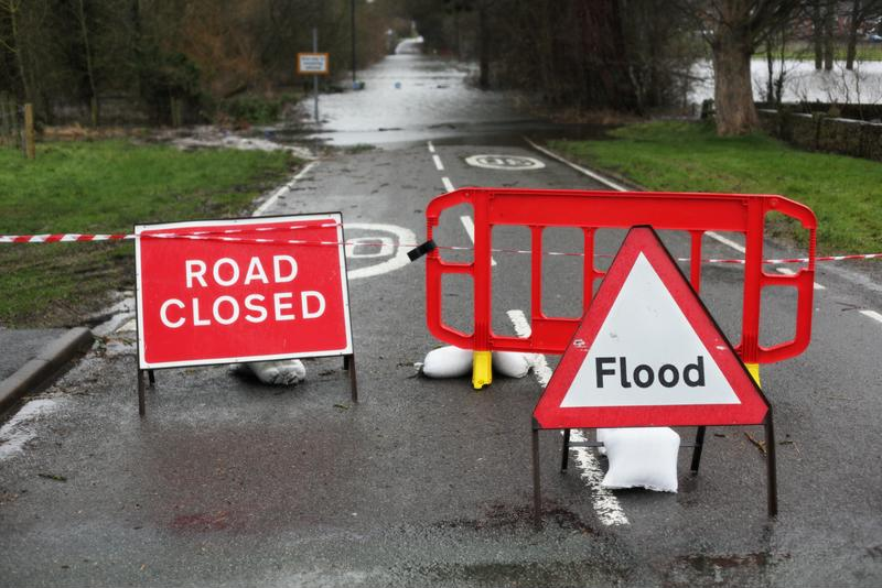 Road sign blocking flooded street.