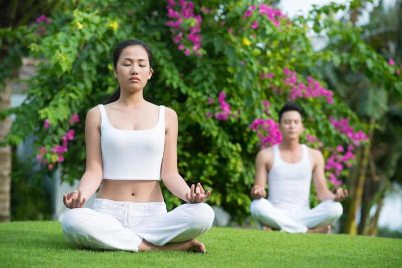 Couple meditating on artificial turf in backyard.