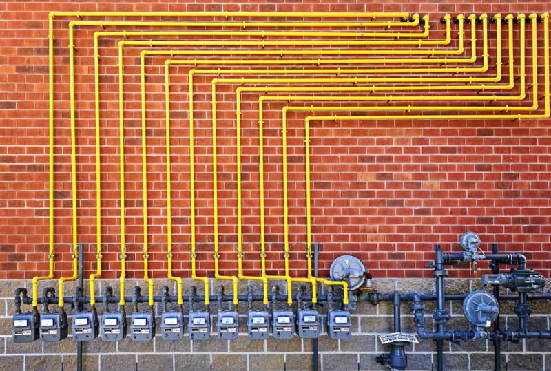 Natural gas lines installed on the outside of a brick building