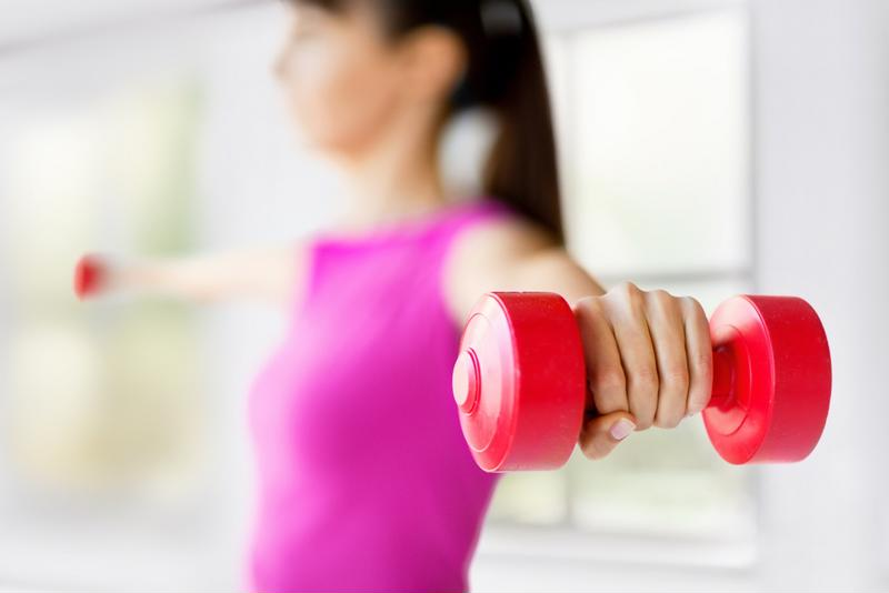 Woman in pink tank top holding barbells with straight arms out to side.