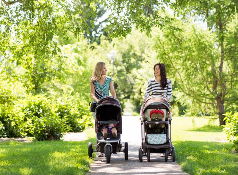 Two moms push strollers with their canopies providing sun for their babies.