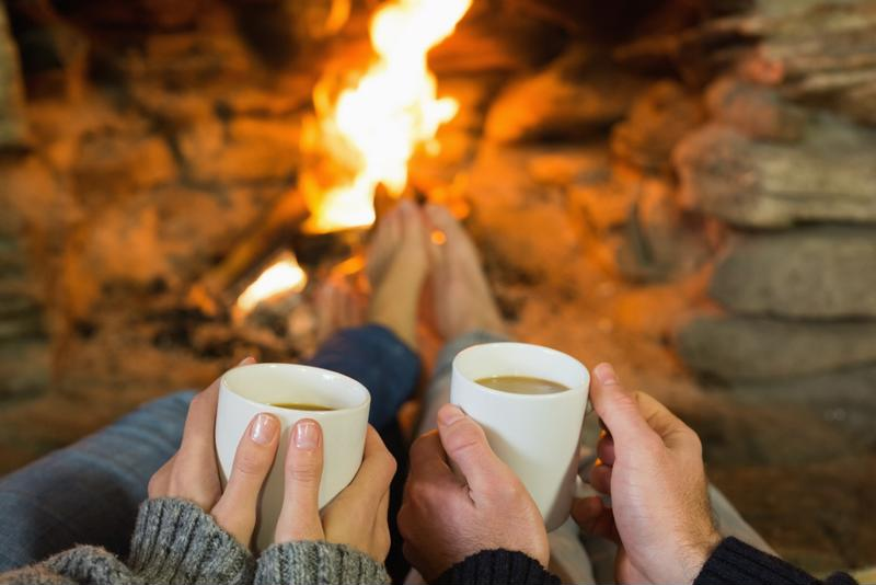 A man and woman sitting next to each other holding mugs of cocoa in front of a fire.