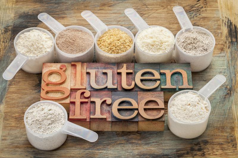 Gluten free sign between measuring cups containing various foods (Rice, quinoa, etc.).
