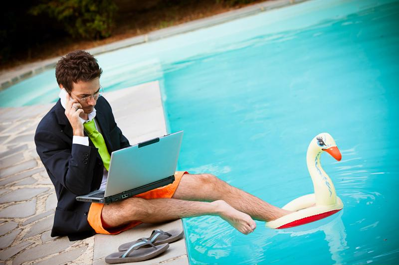 Guy in a suit jacket and tie, with swim trunks on the bottom, sitting poolside with a laptop.