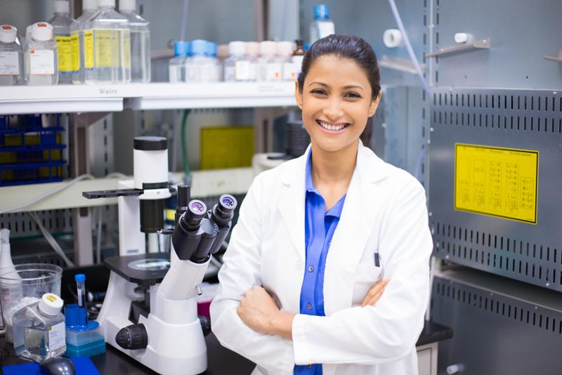 Woman in a white lab coat standing in front of a microscope and other research equipment.