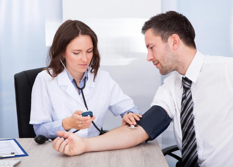 Doctor taking blood pressure of colleague.