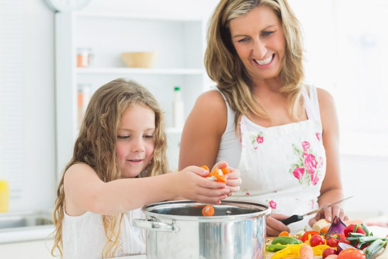 Mother and daughter cooking vegetables.