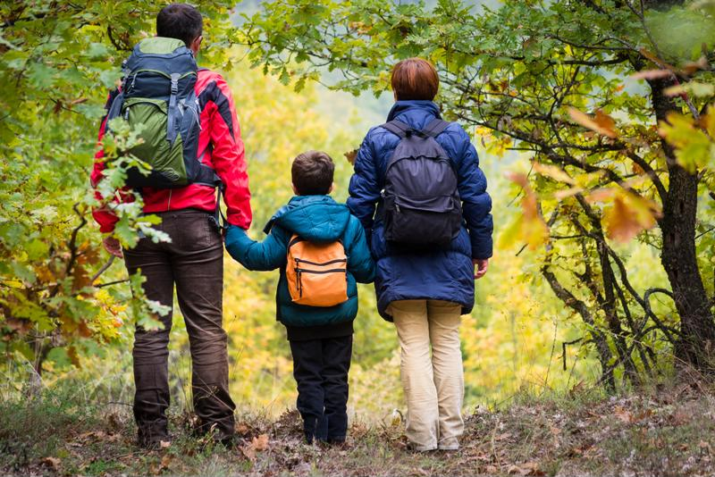 A family of three takes a hiking trip.